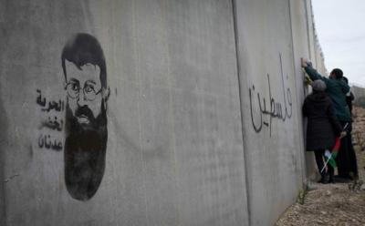 "Graffiti in support of Khader Adnan on the ""apartheid wall"" at Bilin"