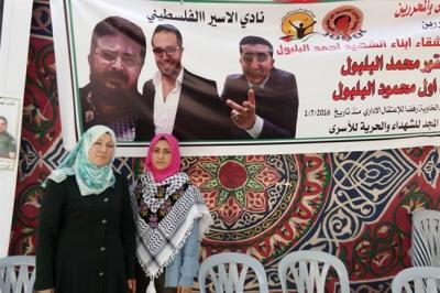 Sanaa Balboul stands with her daughter Nuran in front of a banner dedicated to her slain husband and hunger-striking sons.